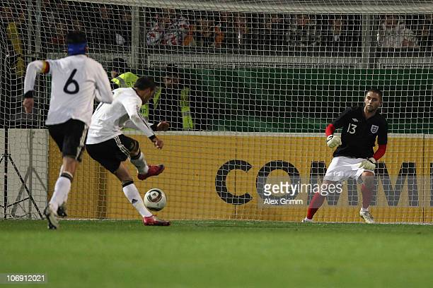 Cenk Torsun of Germany scores his team's second goal with a penalty against Henri Lansbury of England during the U21 international friendly match...