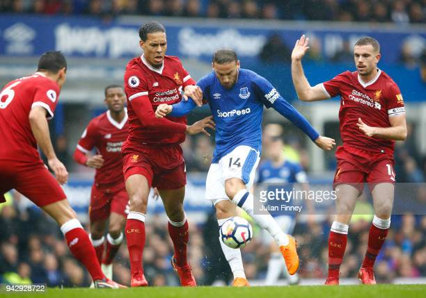 Cenk Tosun of Everton is challenged by Virgil van Dijk of Liverpool and Jordan Henderson of Liverpool during the Premier League match between Everton...