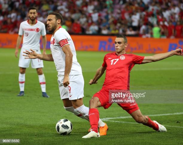 Cenk Tosun of Turkey in action against Ellyes Skhiri of Tunisia during the friendly football match between Tunisia and Turkey at Stade de Geneve in...