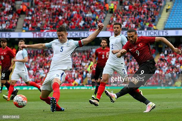 Cenk Tosun of Turkey shoots at goal under prelssure from Gary Cahill of England uring the International Friendly match between England and Turkey at...