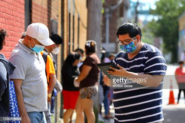 Census 2020 field organizer Jeffrey Tellez, right, interviews a resident in the food pantry line at the Chelsea Collaborative in Chelsea, MA to...