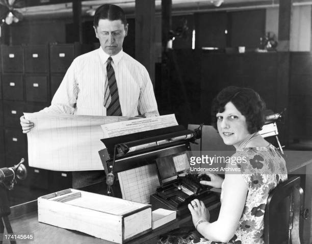 Census Bureau employees work on one of the new machines that will be used to tabulate the 1930 census Washington DC July 20 1929