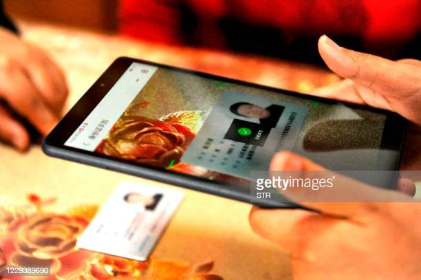 Census workers use an app to collect information from a resident in Qingdao, in China's eastern Shandong province on November 1 as millions of...
