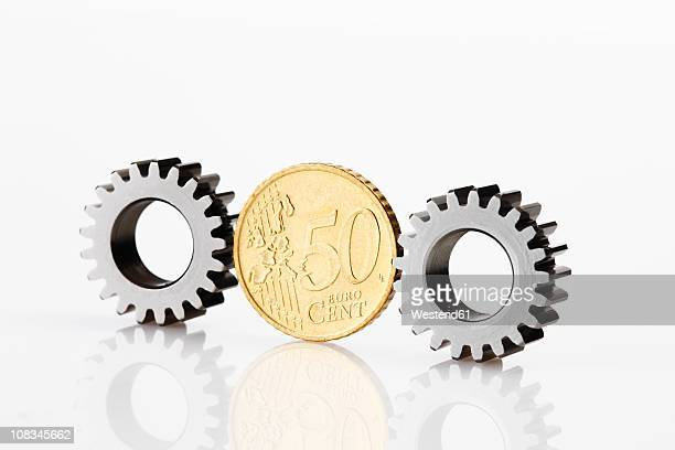 50 cent coin between cogwheels on white background - monetary policy stock pictures, royalty-free photos & images