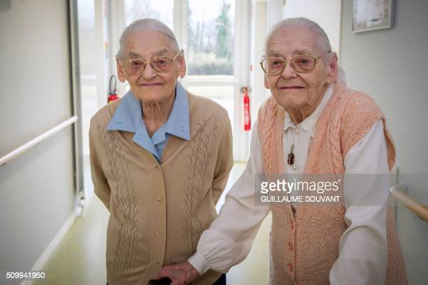"""Centenary twins, Paulette Olivier and Simone Thiot pose in the corridors at the retirement home """"Les Bois Blancs"""" on February 11, 2016. - The twins,..."""