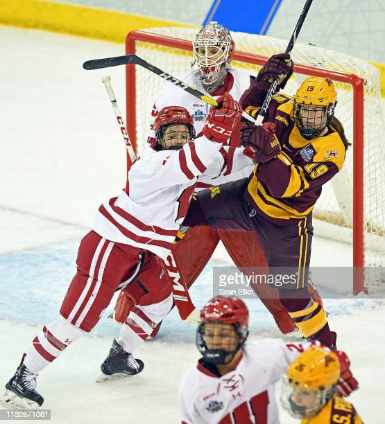 Center Abby Roque of the Wisconsin Badgers pushes center Kelly Pannek of the Minnesota Golden Gophers out of the crease in front of goalie Kristen...