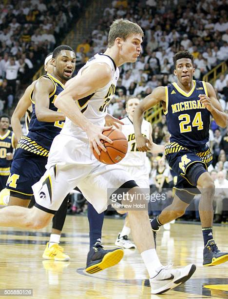 Center Adam Woodbury of the Iowa Hawkeyes drives to the basket against guards Aubrey Dawkins and Zak Irvin of the Michigan Wolverines in the first...