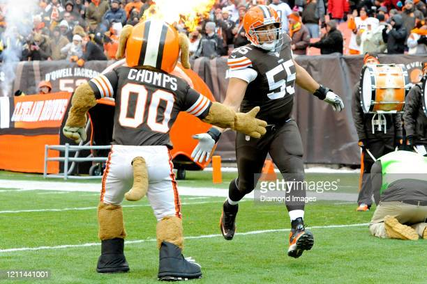 Center Alex Mack of the Cleveland Browns highfives team mascot Chomps during player introductions prior to a game against the Pittsburgh Steelers on...