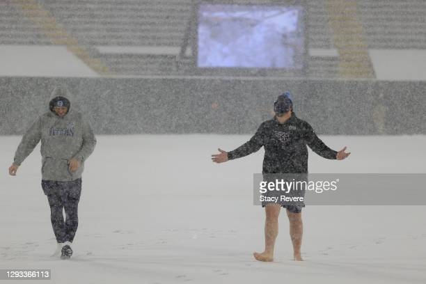 Center Ben Jones of the Tennessee Titans walks barefoot on the snow-covered field with teammate David Quessenberry before a game against the Green...