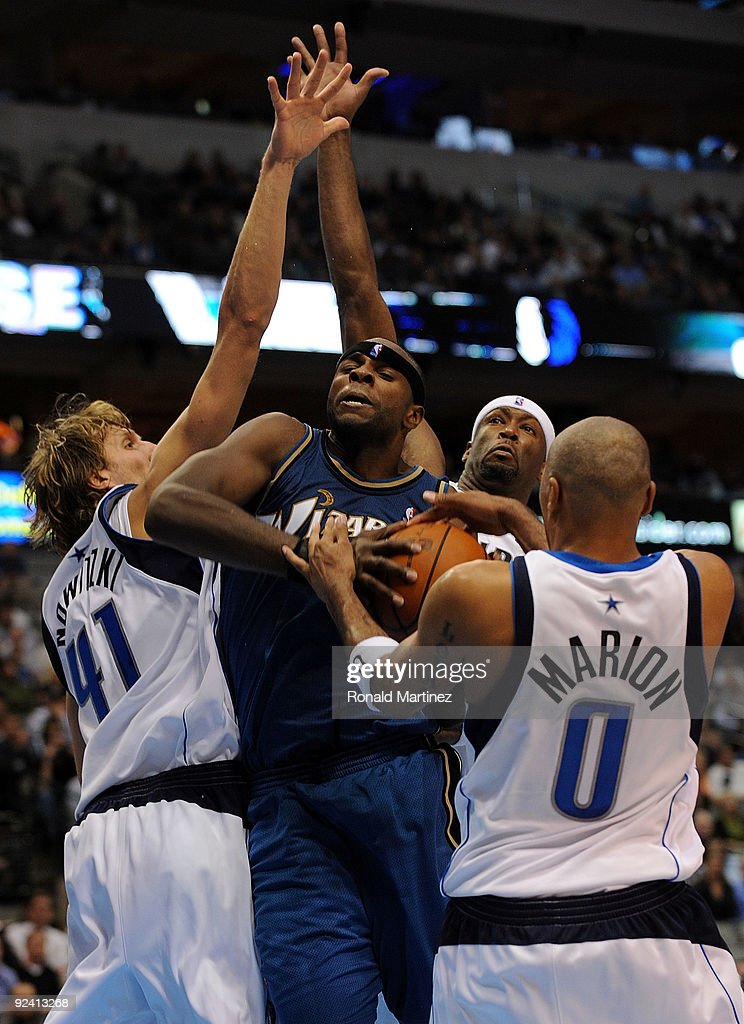 Center Brendan Haywood #33 of the Washington Wizards is tied up with Shawn Marion #0, Dirk Nowitzki #41 and Erick Dampier #25 of the Dallas Mavericks during the season opener on October 27, 2009 at American Airlines Center in Dallas, Texas.