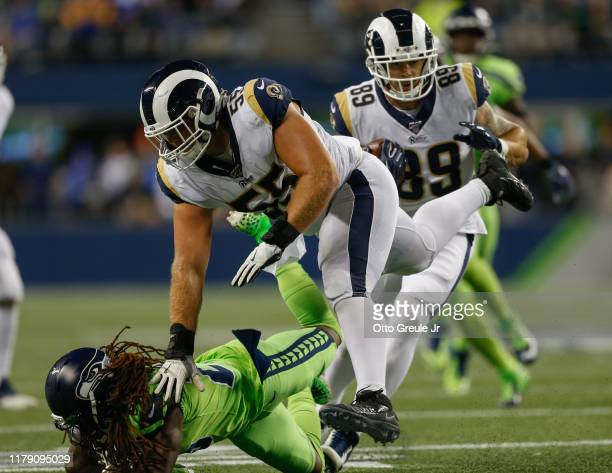 Center Brian Allen of the Los Angeles Rams throws a block against cornerback Shaquill Griffin of the Seattle Seahawks as tight end Tyler Higbee...