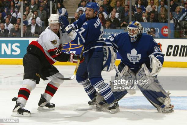 Center Bryan Smolinski of the Ottawa Senators and defenseman Bryan Marchment of the Ottawa Senators fight for position in front of Leafs goalie Ed...
