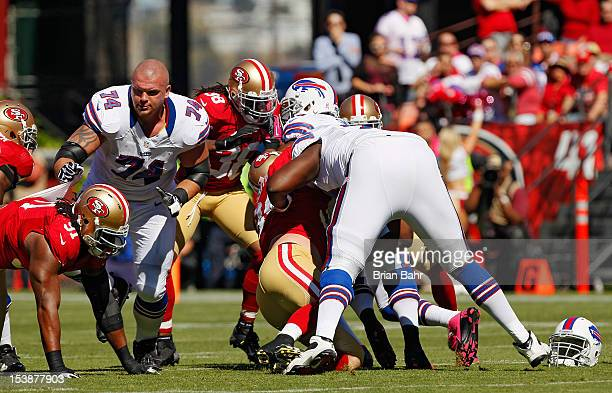 Center Colin Brown of the Buffalo Bills grabs onto the jersey of defensive tackle Ray McDonald of the San Francisco 49ers after losing his helmet on...