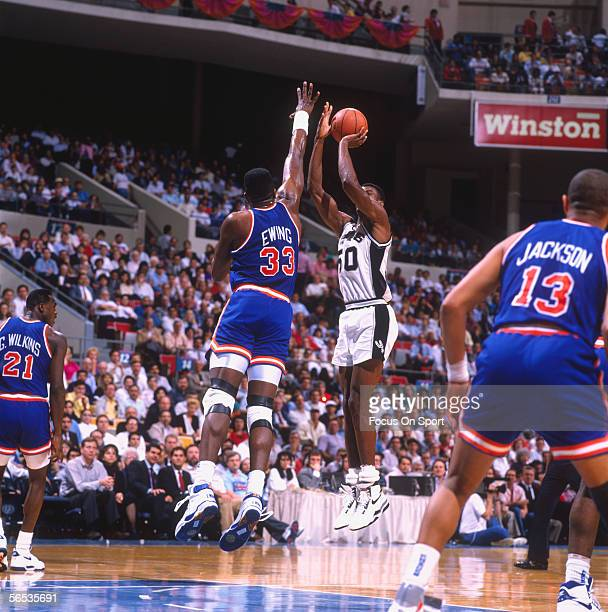 Center David Robinson of the San Antonio Spurs jumps and shoots against blocking Patrick Ewing of the New York Knicks during a game at the Alamodome...