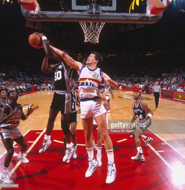 Center David Robinson of the San Antonio Spurs jumps and shoots against the Denver Nuggets but gets completly blocked on the way up during a game at...
