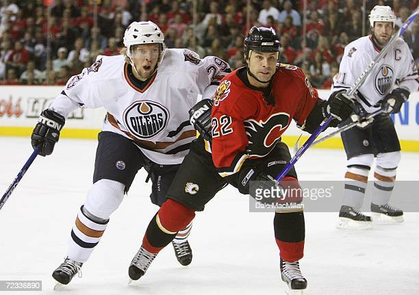 Center Daymond Langkow of the Calgary Flames and defenseman Daniel Tjarnqvist of the Edmonton Oilers chase play at the Pengrowth Saddledome on...