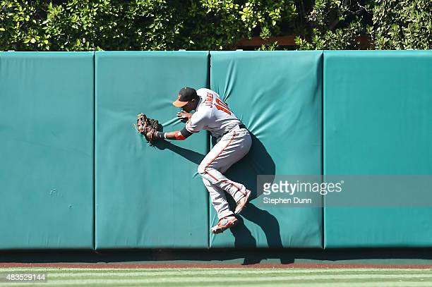 Center fielder Adam Jones of the Baltimore Orioles crashes into the wall after making a running catch on a deep drive by Taylor Featherston of the...
