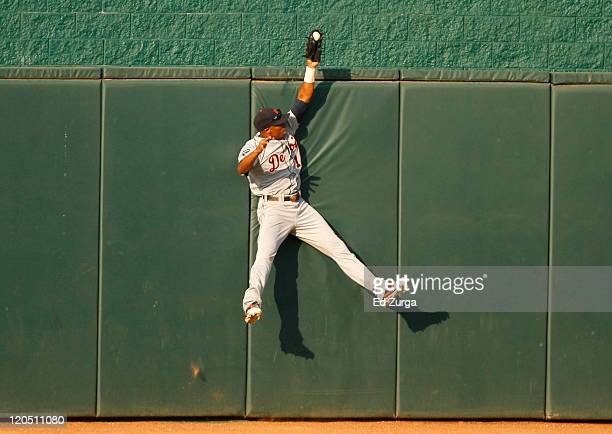 Center fielder Austin Jackson of the Detroit Tigers reaches over the wall as he robs Alex Gordon of the Kansas City Royals of a home run in the first...