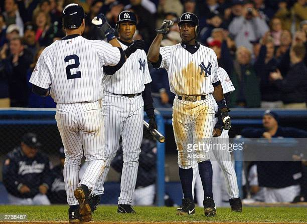 Center fielder Bernie Williams of the New York Yankees and Alfonso Soriano greet Derek Jeter after Jeter and Soriano scored to give the Yankees a 41...
