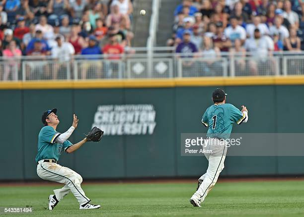 Center fielder Billy Cooke of the Coastal Carolina Chanticleers calls off shortstop Michael Paez to catch the final out against the Arizona Wildcats...