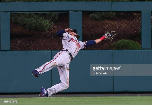 Center fielder Billy Hamilton of the Atlanta Braves dives for a ball hit by J.T. Realmuto of the Philadelphia Phillies during the eighth inning of a...