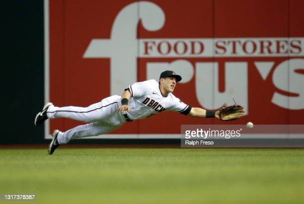 Center Fielder Daulton Varsho of the Arizona Diamondbacks dives in an attempt to catch a line drive triple hit by Jon Berti of the Miami Marlins...
