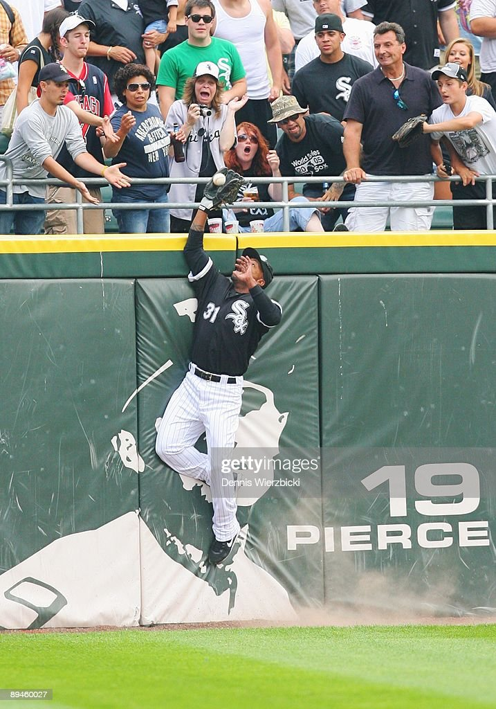 Center fielder Dewayne Wise #31 of the Chicago White Sox leaps over the wall to catch a ball hit by right fielder Gabe Kapler of the Tampa Bay Rays (not pictured) preserving pitcher Mark Buehrle's perfect game in the ninth inning of an MLB game on July 23, 2009 at US Cellular Field in Chicago, Illinois. The White Sox won 5-0. Sequence 1 of 4.