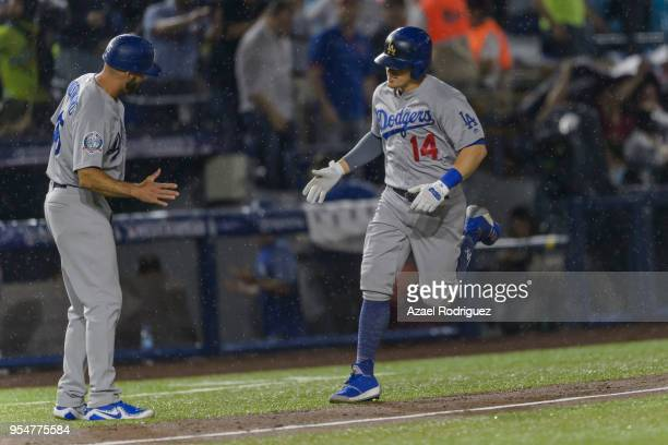 Center fielder Enrique Hernandez of Los Angeles Dodgers celebrates with third base coach Chris Woodward after hitting a solo home run on the second...