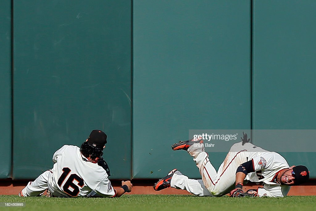 Center fielder Gregor Blanco #7 goes down with an injury after colliding with left fielder Angel Pagan #16 of the San Francisco Giants in the ninth inning against the San Diego Padres at AT&T Park on September 29, 2013 in San Francisco, California. The Giants won 7-6.