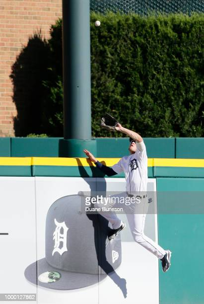 Center fielder JaCoby Jones of the Detroit Tigers climbs the wall to catch a fly ball hit by Adrian Beltre of the Texas Rangers during the sixth...