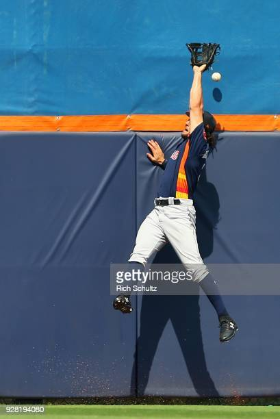Center fielder Jake Marisnick of the Houston Astros attempts to catch a home run by Yoenis Cespedes of the New York Mets during the third inning of a...
