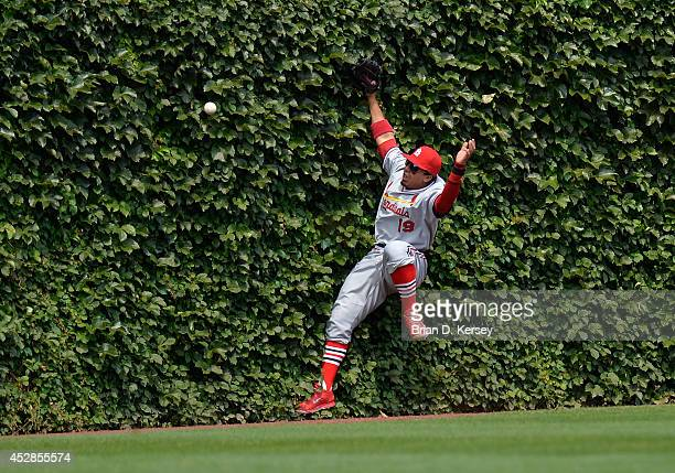 Center fielder Jon Jay of the St Louis Cardinals falls into the wall while trying to catch a double hit by Welington Castillo of the Chicago Cubs...