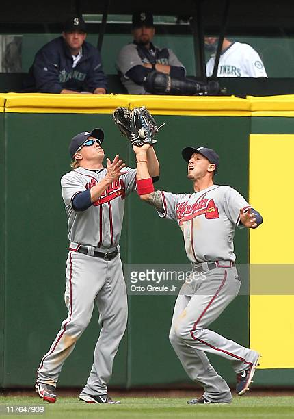 Center fielder Jordan Schafer of the Atlanta Braves makes a catch in front of left fielder Nate McLouth on a deep fly ball by Josh Bard of the...