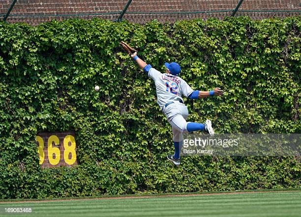 Center fielder Juan Lagares of the New York Mets reaches for but cannot get to a leadoff double hit by David DeJesus of the Chicago Cubs during the...