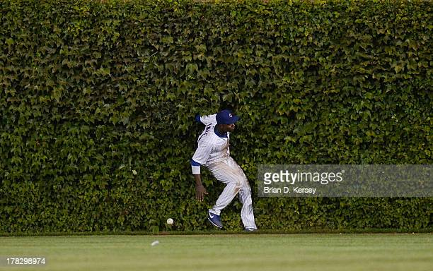 Center fielder Junior Lake of the Chicago Cubs runs into the wall as he tries to field a fly ball hit by Ryan Zimmerman of the Washington Nationals...