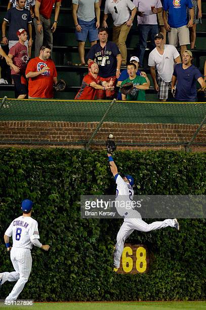 Center fielder Justin Ruggiano of the Chicago Cubs leaps for a grand slam hit by Devin Mesoraco of the Cincinnati Reds as left fielder Chris Coghlan...