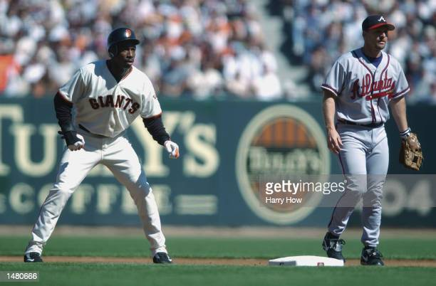 Center fielder Kenny Lofton of the San Francisco Giants leads off second base as second baseman Keith Lockhart of the Atlanta Braves keeps him close...