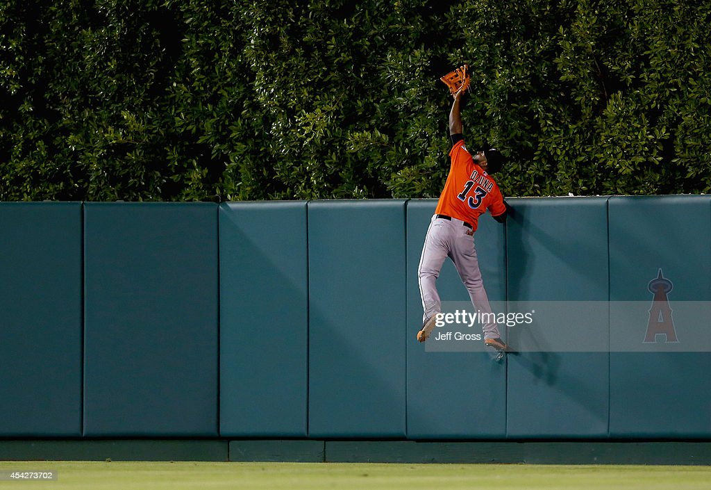 Center fielder Marcell Ozuna #13 of the Miami Marlins leaps but can't come down with a ball hit by Mike Trout of the Los Angeles Angels of Anaheim resulting in a solo home run in the seventh inning at Angel Stadium of Anaheim on August 27, 2014 in Anaheim, California.
