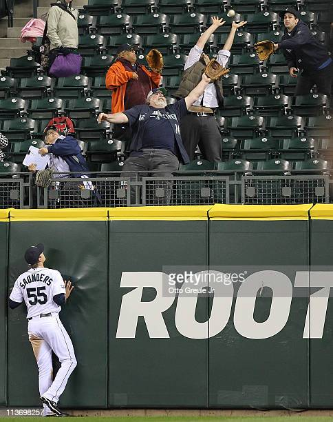Center fielder Michael Saunders of the Seattle Mariners watches a home run by Chris Davis of the Texas Rangers land in the bleachers at Safeco Field...