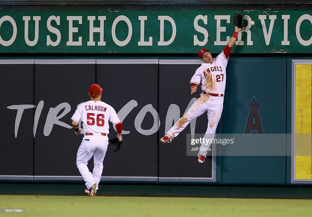 Center fielder Mike Trout #27 of the Los Angeles Angels of Anaheim can't make the catch on a ball hit by Jeff Baker of the Miami Marlins resulting in a triple, as Kole Calhoun #56 looks on in the eighth inning at Angel Stadium of Anaheim on August 27, 2014 in Anaheim, California.
