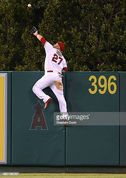 Center fielder Mike Trout of the Los Angeles Angels of Anaheim jumps at the wall and makes the catch to take a home away from Jesus Montero of the...
