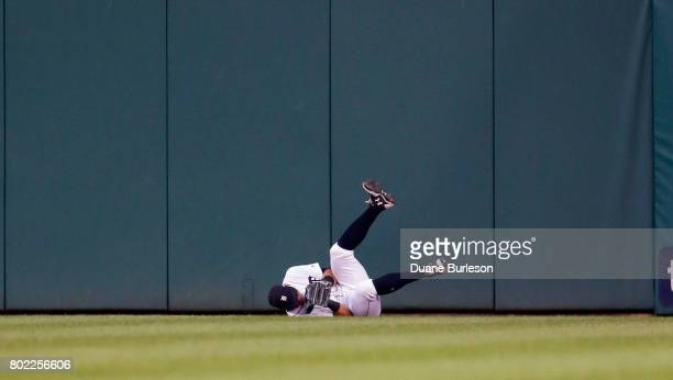 Center fielder Mikie Mahtook of the Detroit Tigers falls to the field after making a leaping catch of a ball hit by Salvador Perez of the Kansas City...