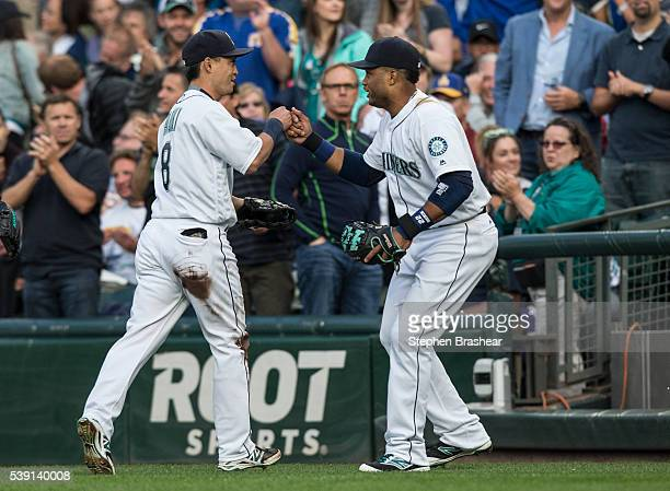 Center fielder Norichika Aoki of the Seattle Mariners is congratulated by second baseman Robinson Cano after Aoki made a catch on the run on a ball...