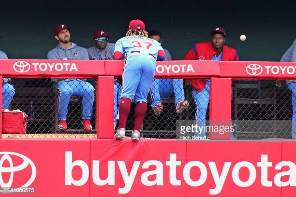 Center fielder Odubel Herrera of the Philadelphia Phillies climbs the wall and looks at the ball hit by Christian Yelich of the Milwaukee Brewers for...