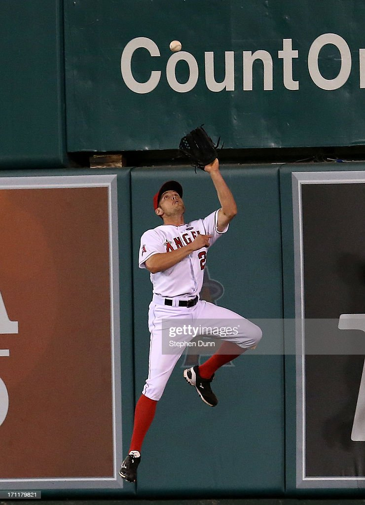 Center fielder Peter Bourjos #25 of the Los Angeles Angels of Anaheim makes a leaping catch at the wall on a drive by Andrew McCutchen of the Pittsburgh Pirates to end the top of the ninth inning at Angel Stadium of Anaheim on June 22, 2013 in Anaheim, California.