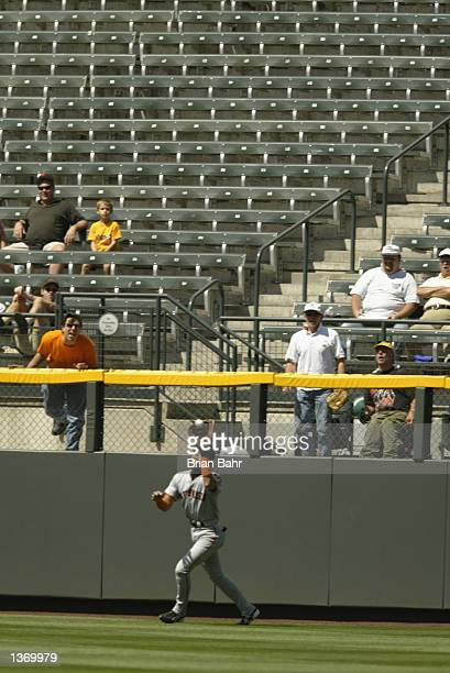 Center fielder Tsuyoshi Shinjo of the San Francisco Giants catches a deep fly ball as one of a few fans in the outfield yells at him in a game...