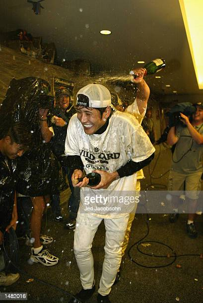Center fielder Tsuyoshi Shinjo of the San Francisco Giants celebrates with teammates after they clinch the National League wild card with the victory...