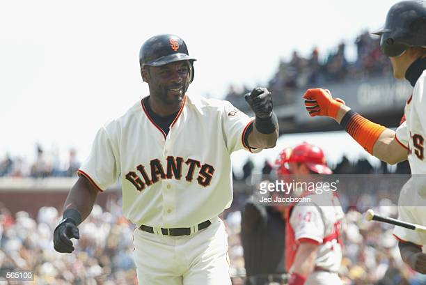 Center fielder Tsuyoshi Shinjo of the San Francisco Giants greets right fielder Reggie Sanders after his gamewinning home run during the MLB game...
