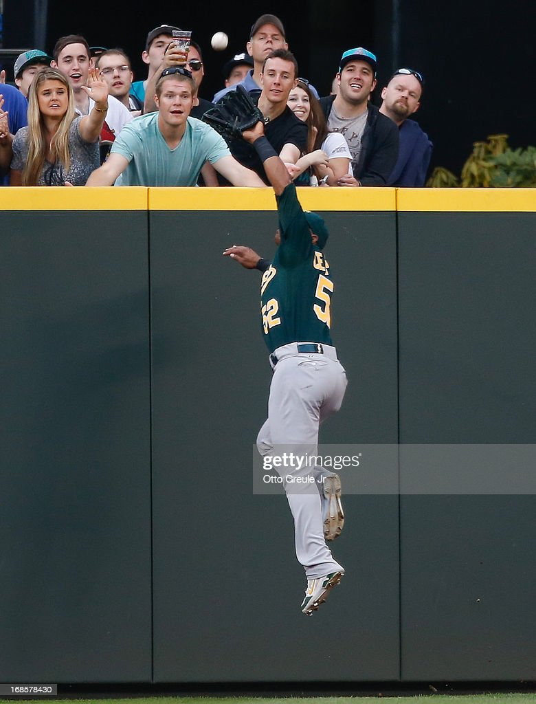 Center fielder Yoenis Cespedes #52 of the Oakland Athletics makes a leaping catch on a deep fly ball by Kyle Seager of the Seattle Mariners in the sixth inning at Safeco Field on May 11, 2013 in Seattle, Washington.