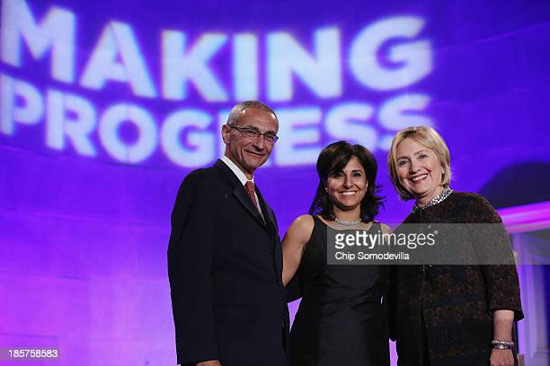 Center for American Progress cofounder John Podesta center President Neera Tanden and former Secretary of State Hillary Clinton pose for photographs...